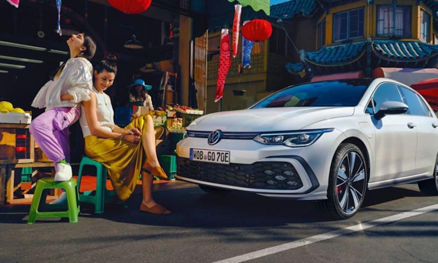 VW Volkswagen Golf GTE i fargen hvit, sett skrått forfra, står på gaten, 2 kvinner sitter foran