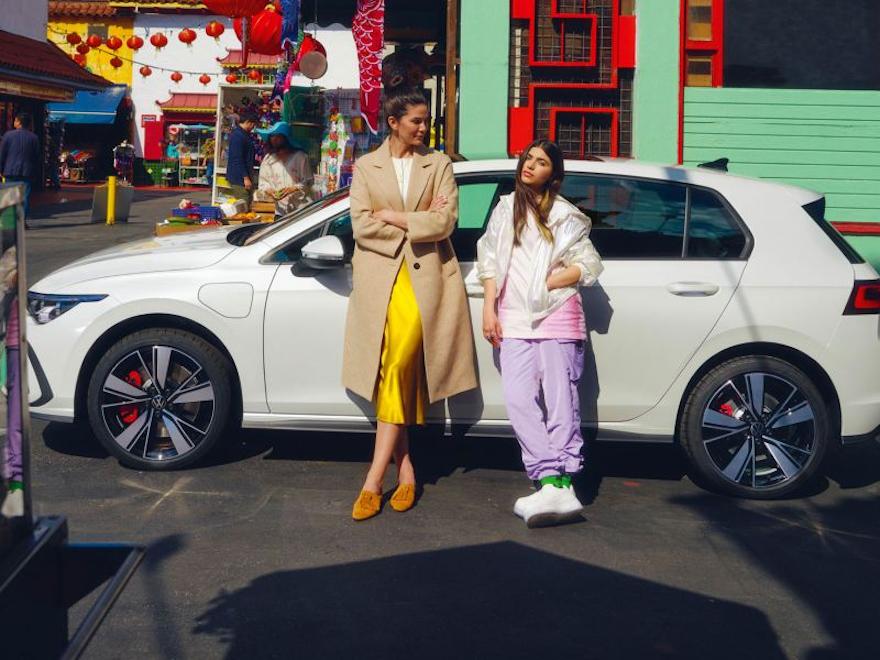 2 kvinner lener seg mot Volkswagen VW Golf GTE, sett fra siden